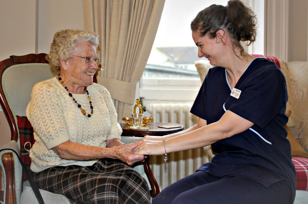 Resident and Parade House staff member enjoying a conversation together at Parade House in Monmouth